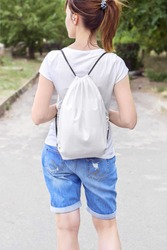 Woman with drawstring bag on the shoulder. Cropped.
