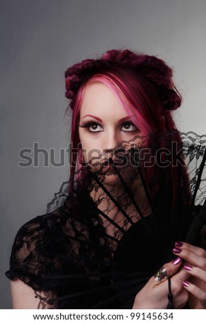 woman with dread lock hair holding a fan up to her face - stock photo