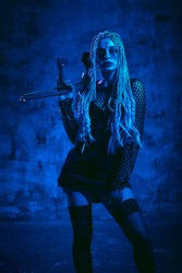 Woman with dreadlocks and stigmata Halloween outfit posing with on a blue background. Gorgeous girl in clothes celebrates the day of the dead. Halloween concept, witch costume, bright colors, blue