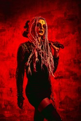 Woman with dreadlocks and stigmata Halloween outfit posing with on a red background. Gorgeous girl in clothes celebrates the day of the dead. Halloween concept, witch costume, bright colors, steam