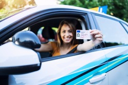 Woman with driving license. Driving school. Young beautiful woman successfully passed driving school test. Female smiling and holding driver's license.