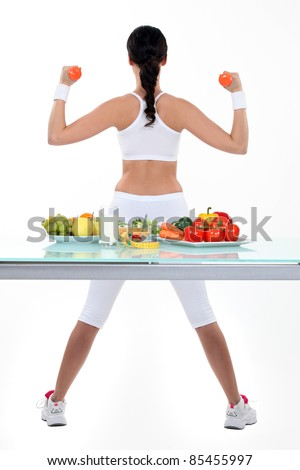 Woman with dumbbells and plates of salad and fruit