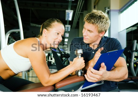 Woman with dumbbells in a gym, her personal trainer gives a report on her training