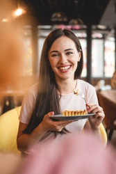 woman with exquisite smile and beautiful eyes having breakfast with her friend in a cozy cafe. She eats a fork a piece of cake and drinks tea sitting in a chair at a table
