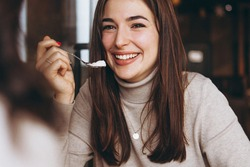 woman with exquisite smile and beautiful eyes having breakfast with her friend in a cozy cafe. She drinks latte sitting in a chair at a table