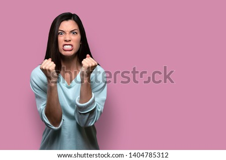 Woman with extreme rage, clinched fists and jaw, angry, emotional, and furious, isolated on pink background, copy space Сток-фото ©