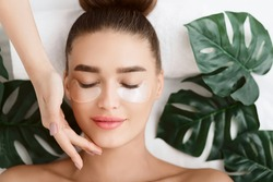 Woman With Eye Patches, Relaxing In Spa Center With Leaves Nearby, Top View