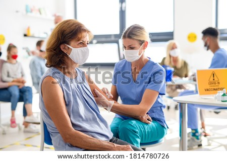 Woman with face mask getting vaccinated, coronavirus, covid-19 and vaccination concept.