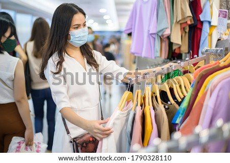 woman with face mask is shopping clothes in Shopping center woman with face mask is shopping clothes in Shopping center .