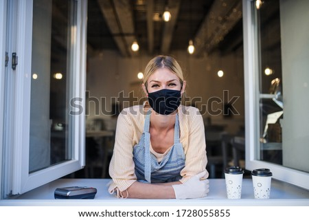 Woman with face mask serving coffee through window, shop open after lockdown.