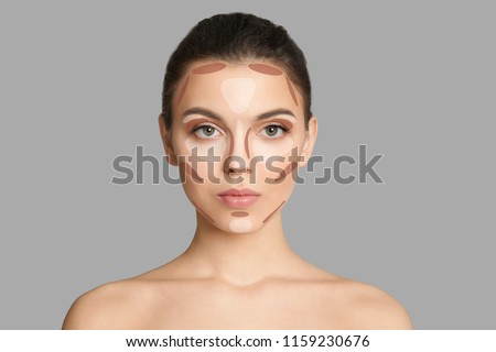 Woman with facial makeup contouring map on grey background. Professional tutorial