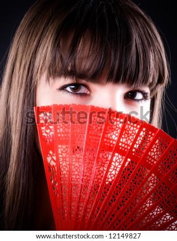 Woman with fan portrait. On black background.