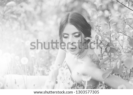 woman with fashionable makeup and beads in green leaves and dandelion flower on natural background, beauty and fashion, youth and freshness #1303577305