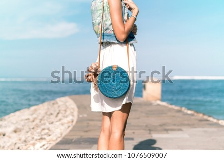 Woman with fashionable stylish blue rattan bag and silk scarf outside. Tropical island of Bali, Indonesia. Rattan handbag and silk scarf.