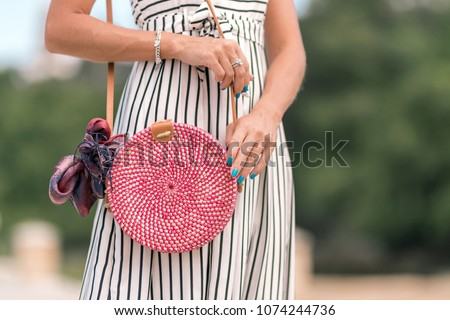 Woman with fashionable stylish red rattan bag and silk scarf outside. Tropical island of Bali, Indonesia. Rattan handbag and silk scarf.