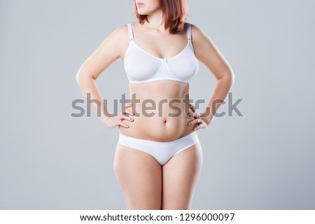 Woman with fat abdomen, overweight female body on gray background, studio shot