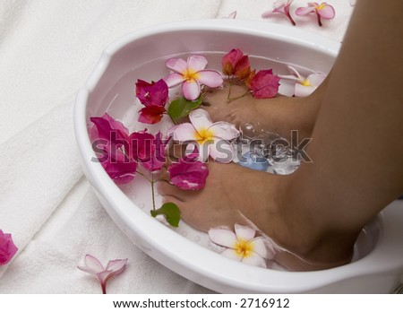 Woman with feet in a foot bath filled with water and flowers