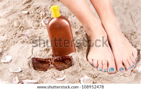 Woman with feet in the sand with sunglasses and sunscreen.