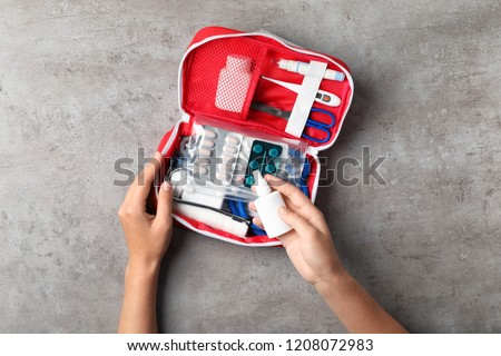 Woman with first aid kit on gray background, top view #1208072983