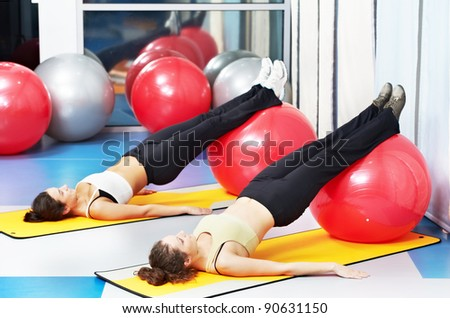 woman with fitness ball in gym at physical training in sport wear - stock photo