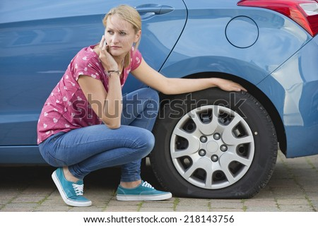 Woman With Flat tire On Car Phoning For Assistance