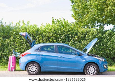 Woman With Flat Tyre On Car Resting Feet On Suitcase