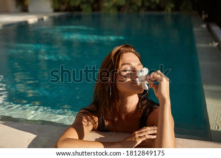 Woman with flower in her hand relaxing in outdoor swimming pool in Bali luxury resort. Beautiful young woman smell  flowers at swimming pool