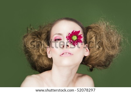 Woman with flower on eye and fluffy hair.