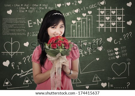 Woman with flowers standing in front of the formula of love
