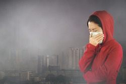 Woman with flu sneezing, woman dressed pink in winter clothing wearing mask to her nose in a cold and flu health concept against