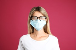 Woman with foggy glasses caused by wearing disposable mask on pink background. Protective measure during coronavirus pandemic