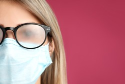 Woman with foggy glasses caused by wearing disposable mask on pink background, space for text. Protective measure during coronavirus pandemic