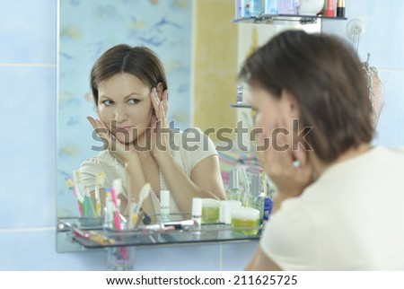 Woman with fresh skin of face in bathroom