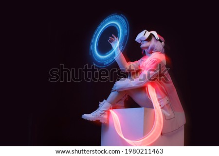 Woman with futuristic tablet in hand. Girl in glasses of virtual reality presses the start button. Augmented reality game, future technology, AI concept. Holographic interface to display data.