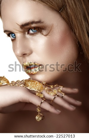 woman with gold leaf lips and gold bracelet visible moisture on her face
