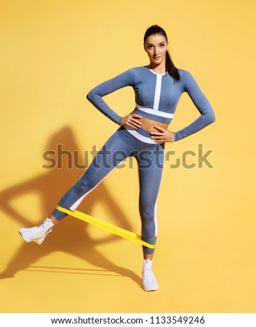 Woman with good physique doing stretching work out with elastic bands. Photo of latin woman in fashionable sportswear on yellow background. Strength and motivation.