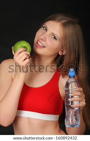 Woman with green apple and bottle of mineral water