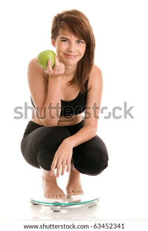Woman with green apple crouching on scale