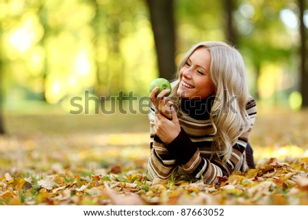 woman with green apple in autumn park