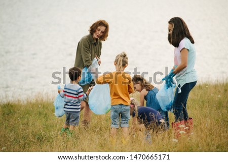 Woman with group of kids collecting garbage on a meadow next to the river on a cloudy summer day. Environmental pollution. Ecological problem. #1470665171