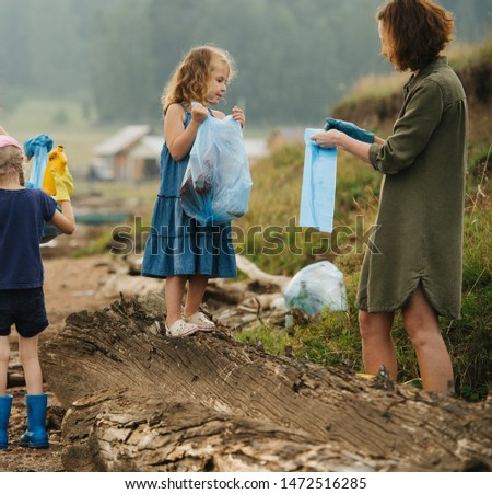 Woman with group of  kids collecting glass and plastic bottles in garbage bags along the river shore on a cloudy summer day. Environmental pollution. Ecological problem. #1472516285