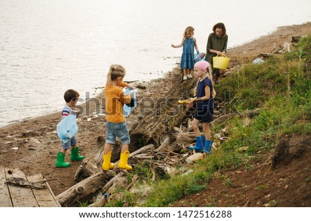 Woman with group of small kids in colored rubber boots collecting garbage on a river shore on a cloudy summer day. Environmental pollution. Ecological problem. #1472516288