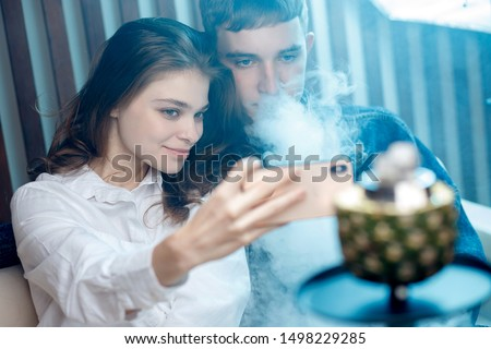 Woman with guy hookah, blow smoke from tobacco and take selfie photo on phone, blue shisha background.