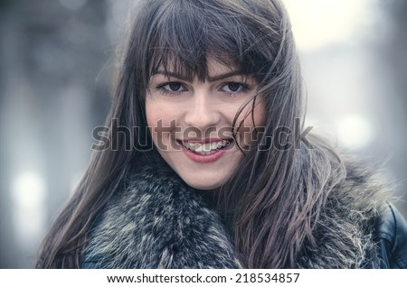 Woman with hair blowing in the wind with a blurred nature background. Winter cold weather, close up shot of beautiful girl, outdoors