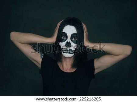 Woman with Halloween skull makeup holding her head with fear emotions
