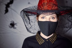 Woman with Halloween witch costume wearing red hat and protection mask. Halloween on quarantine coronavirus pandemic. Dark background with spiders, spiderwebs and bats.