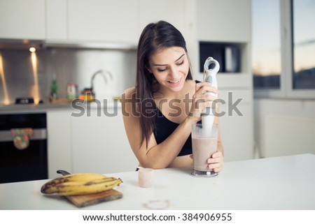 Woman with hand blender making sweet banana chocolate protein powder milkshake smoothie.Drinking protein shake after workout.Whey,banana,low fat milk sport nutrition diet after gym.Healthy lifestyle