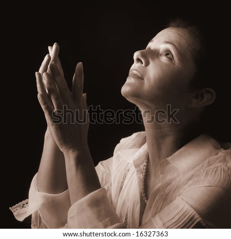 Woman with hands folded in prayer, looking up to a heavenly light