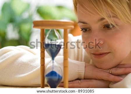 Woman with happy memories daydreaming by a hourglass - shallow DOF