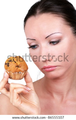 Woman with Hard diet choice looking at tasty cake in hand